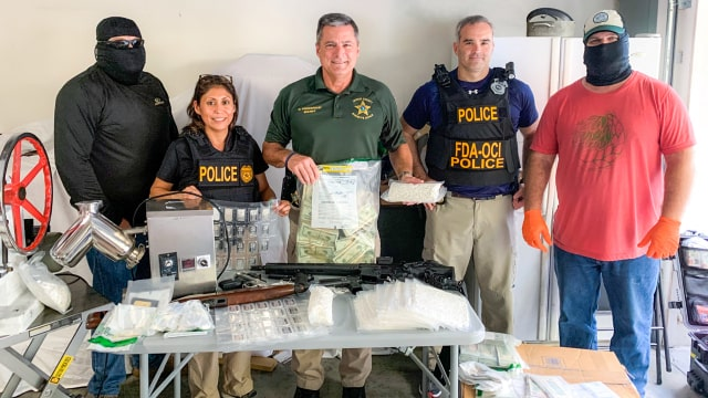 A picture of Law enforcement officers pose with items seized during the investigation